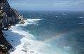 Storm winds driving sea spray very high make rainbows over the cliffs at Cape Point